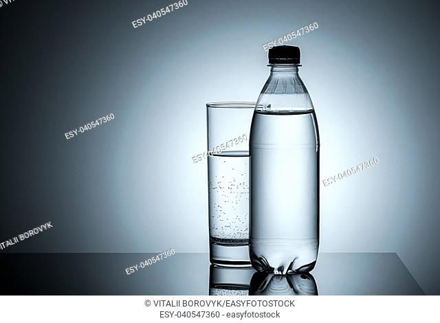 Plastic bottle and glass with water. Gradient background
