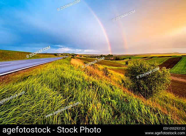Spring rapeseed and small farmlands fields after rain evening view, cloudy sunset sky with colorful rainbow and rural hills