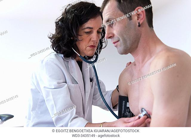 A female doctor checking the heart health of a man with a stethoscope