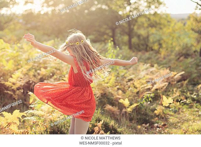 Little girl wearing red summer dress dancing in nature