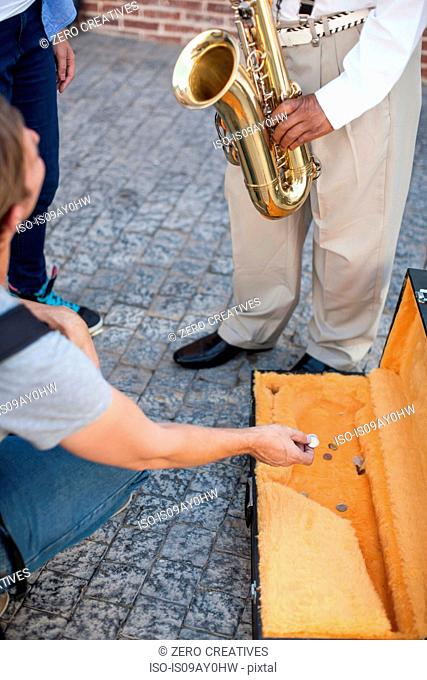 Pedestrian throwing money into street musician's music case, low section