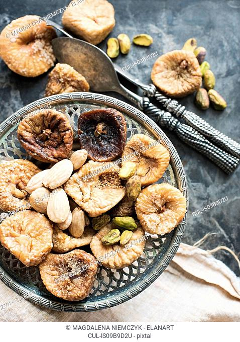 Dried figs and nuts served on antique plate, close-up