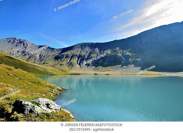 Lac du Goléon appears in deep turquoise colour with the first sunlight in early morning, Hautes-Alpes, French Alps, France