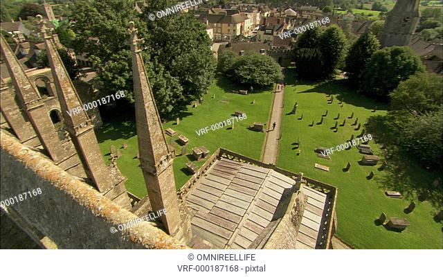 View from balcony of Malmesbury Abbey with graveyard below and village and fields beyond