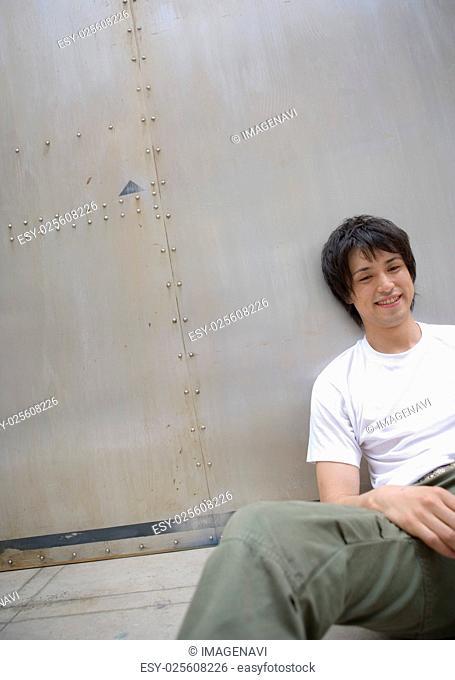 Man sitting by wall