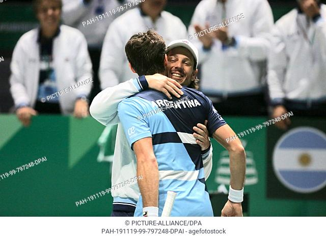 19 November 2019, Spain, Madrid: Tennis, Men: Davis Cup - Group stage, Group C, Pella (Argentina) - Jarry (Chile): Guido Pella (l) celebrates his win with coach...