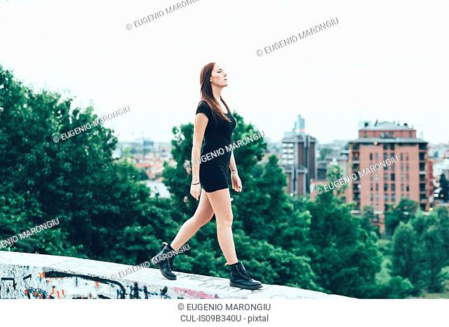 Young woman in mini dress walking on wall above city