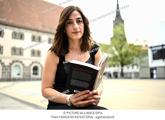 "24 April 2019, Baden-Wuerttemberg, Ulm: The journalist Mesale Tolu holds her book """"My son stays with me"""" in her hand. About eight months after her return to..."