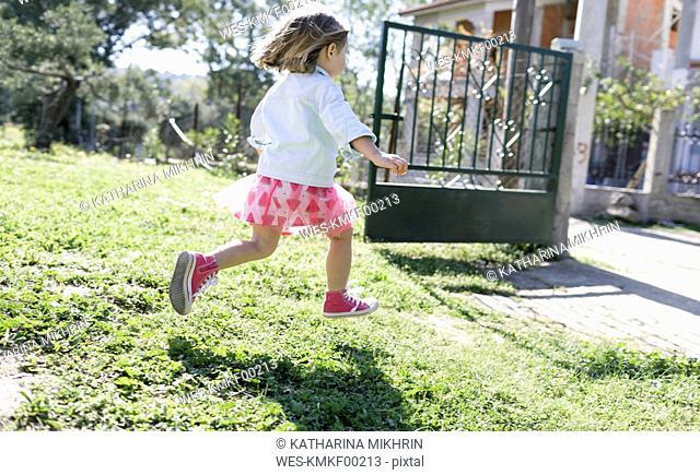 Little girl running on meadow in the garden