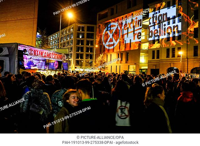 """12 October 2019, Berlin: Numerous young people dance in front of an improvised music stage with the banner """"""""Klimanotstand"""""""" under a projection of the..."""