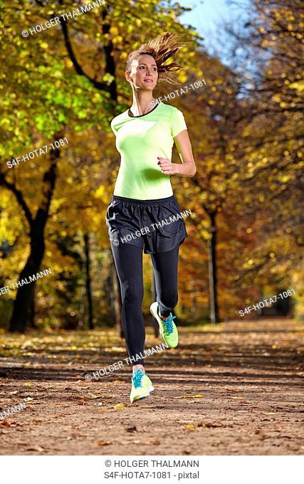 Frau joggt in herbstlichem Wald