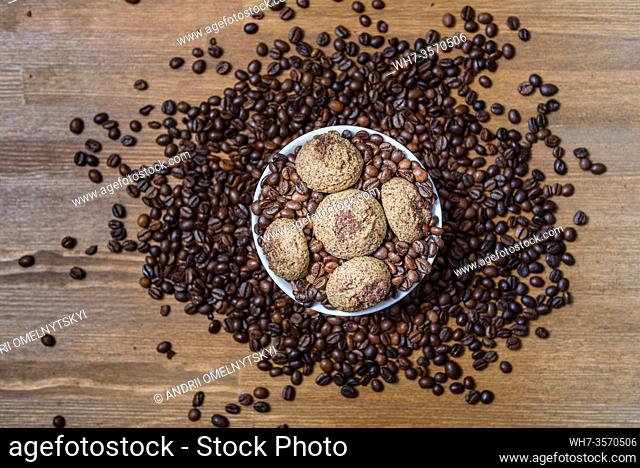 coffee cookies in a white plate with coffee beans on wooden brown table