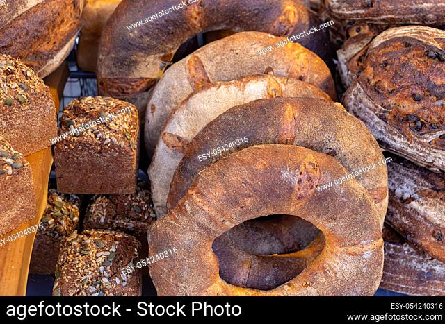 Variety of freshly baked rustic bread loaves on display on a food market stall in the UK