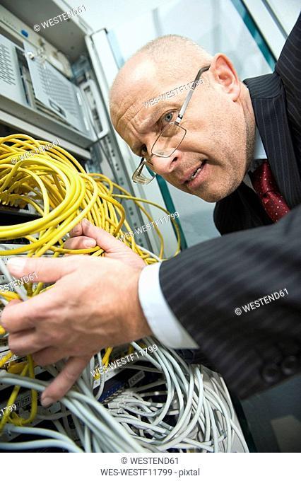 Germany, Munich, Business man checks connectivity on a computer server rack
