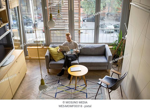 Man drinking coffee and reading newspaper in his living room