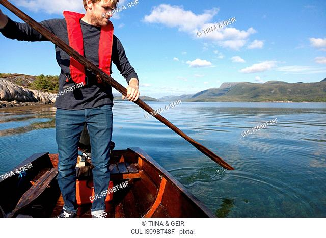 Mature man standing up to use oar in rowing boat, Aure, More og Romsdal, Norway