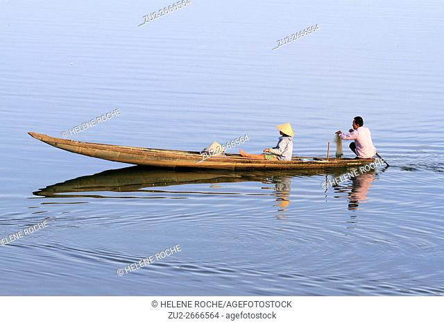 Fisherman on Hue river in traditional wooden canoe, Hue, Vietnam, Asia