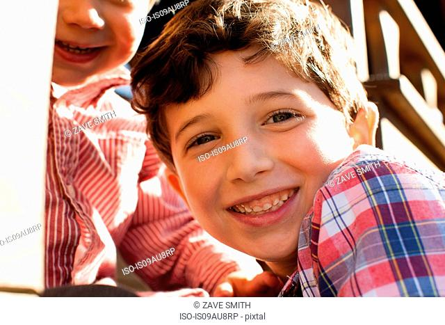 Close up of boy with big brother looking at camera smiling