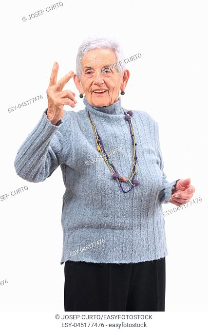 Older woman making the victory sign on a white background