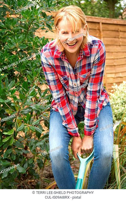 Portrait of mature woman having fun digging garden