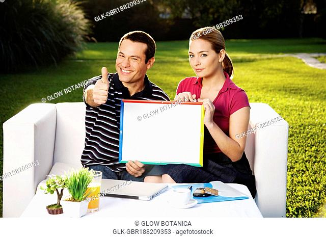 Man holding a picture frame and showing thumbs up sign