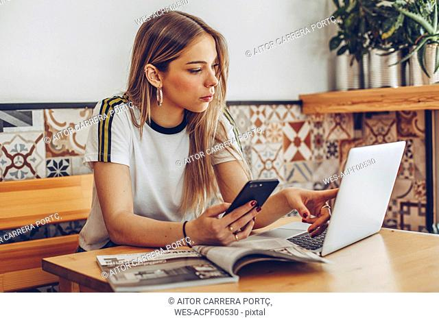 Young woman using mobile phone and laptop in cafe