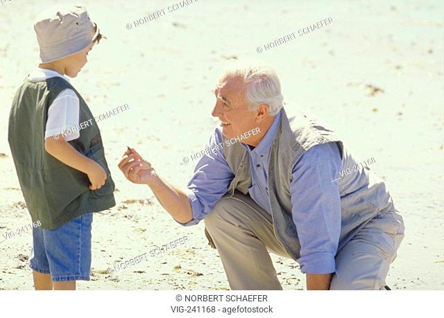 portrait, scene, grandfather with his grandson searching for pebbles at the beach  - GERMANY, 25/01/2004
