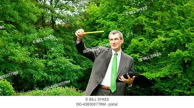Businessman measuring distance in park