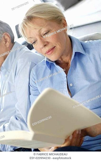 Senior woman reading book, husband sitting beside her