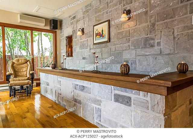 Caramel coloured leather armchair and grey cut stone wall with walnut wood top in dining room with varnished walnut floorboards inside an old 1877 French regime...