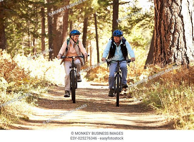 Senior couple mountain biking on forest trail, California