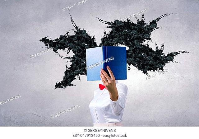 Woman with opened book against her face and black splashes coming from pages