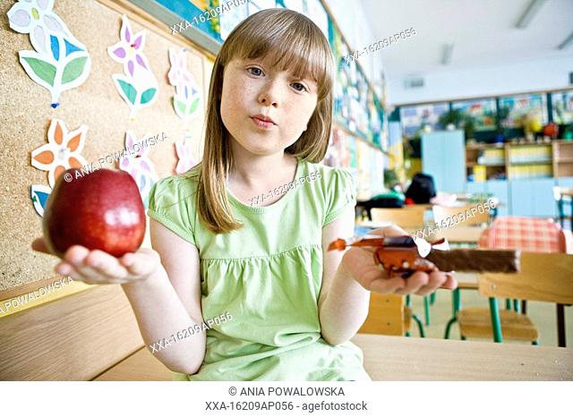 girl at school with apple and chocolate