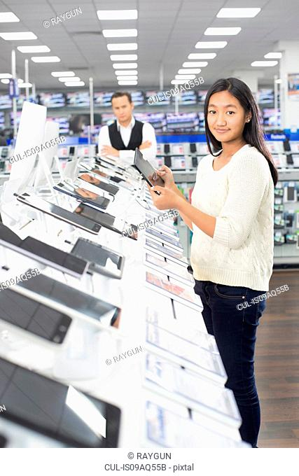 Portrait of young female shopper browsing digital tablets in electronics store