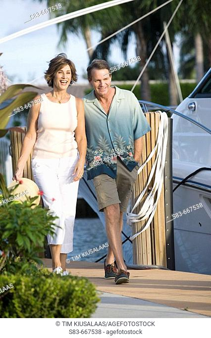 Couple walking down dock with boats in the background