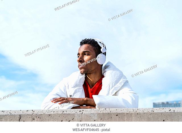 Young man listening to music with headphones outdoors