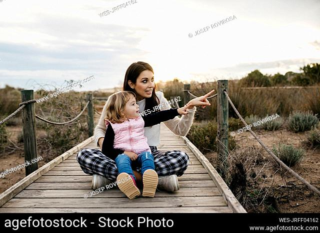 Happy mother and daughter sitting on a boardwalk in the countryside
