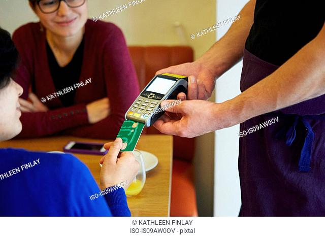 Cropped shot of woman inserting card into credit card machine in restaurant