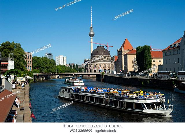 Berlin, Germany, Europe - Excursion boats with tourists travel up and down The Spree river in Berlin Mitte. The Bode Museum and the TV tower at Alexanderplatz...