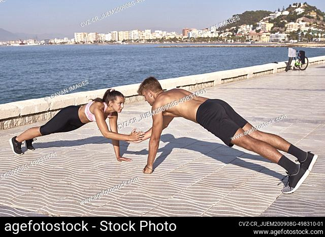 Young man and woman athletes train in a public park