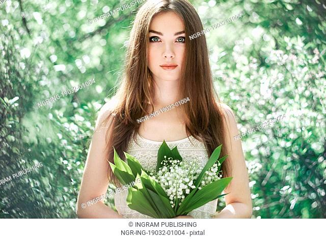 Portrait of beautiful young woman with lily of the valley. Girl on nature. Spring flowers. Fashion beauty
