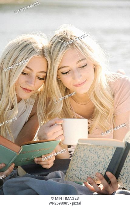 Two blond sisters lying on a jetty, reading a book