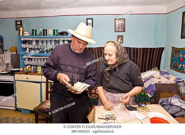 Rumanian couple flicking through a photo album in Bezded, Salaj, Transylvania, Rumania, Europe