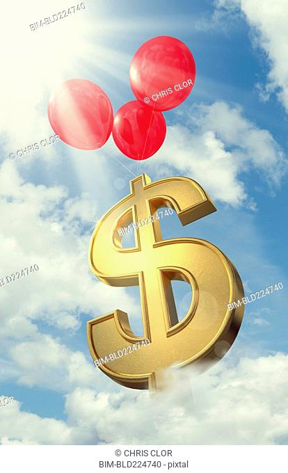 Red balloons lifting dollar symbol in cloudy sky