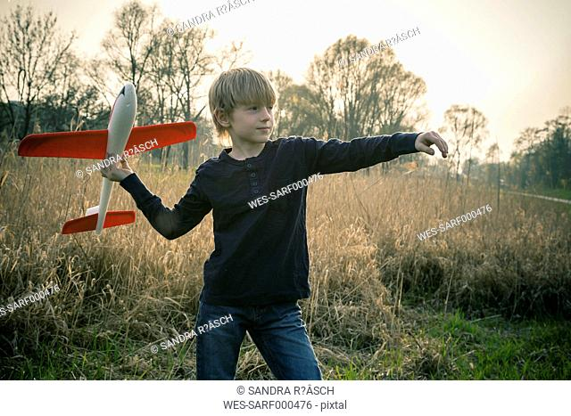 Germany, Bavaria, Landshut, Boy playing with toy aeroplane