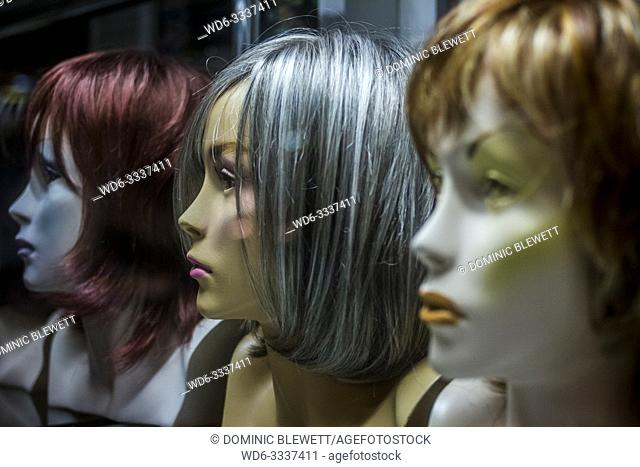 Wigs displayed on mannequin heads in a shop window at night in Poznan, Poland