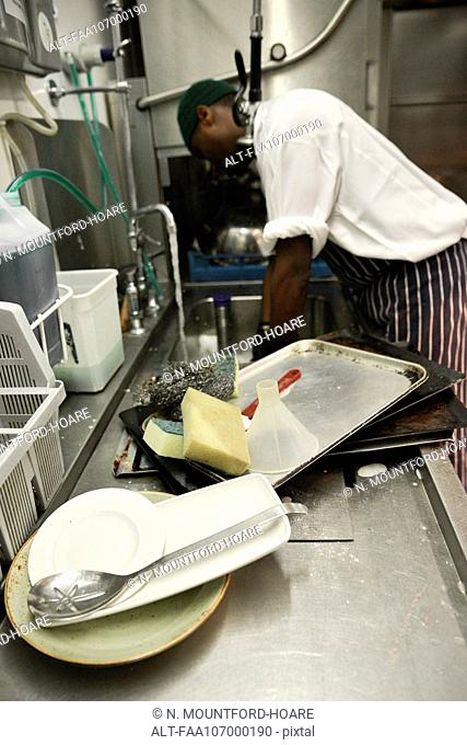 Worker washing dishes in commercial kitchen
