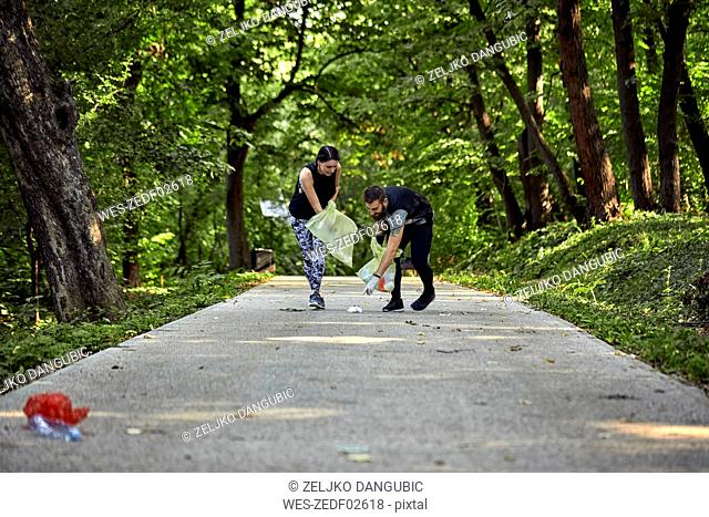 Couple plogging on forest path