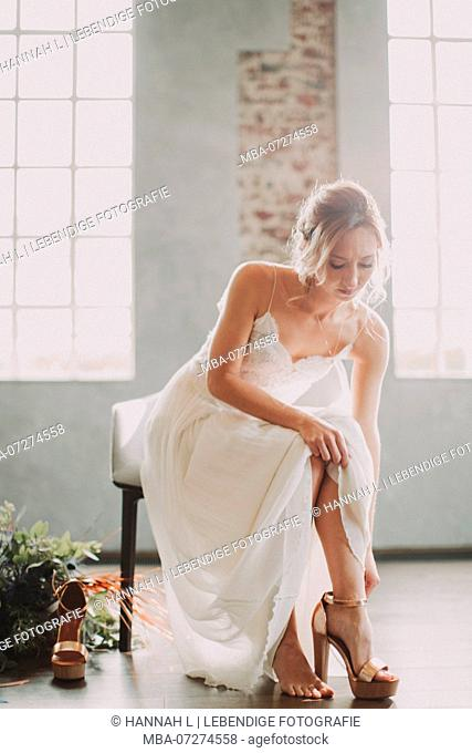 Bride, sitting, puts on her shoes