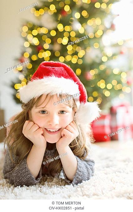 Portrait smiling girl wearing Santa hat on rug in living room with Christmas tree
